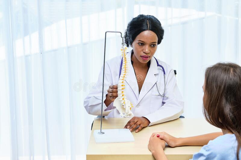 Black African female doctor explain anatomy and medical treatment to female patient with Spinal bone structure model. Used by chiropractic doctor. health care royalty free stock image