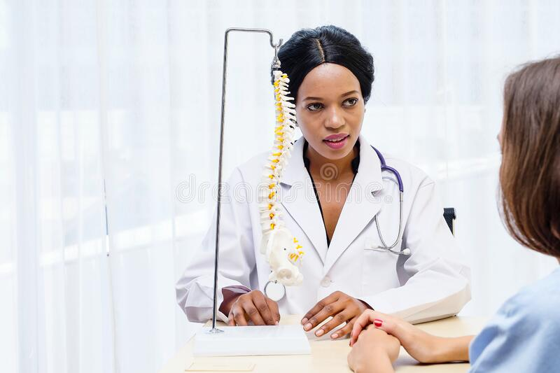 Black African female doctor explain anatomy and medical treatment to female patient with Spinal bone structure model. Used by chiropractic doctor. health care stock photography