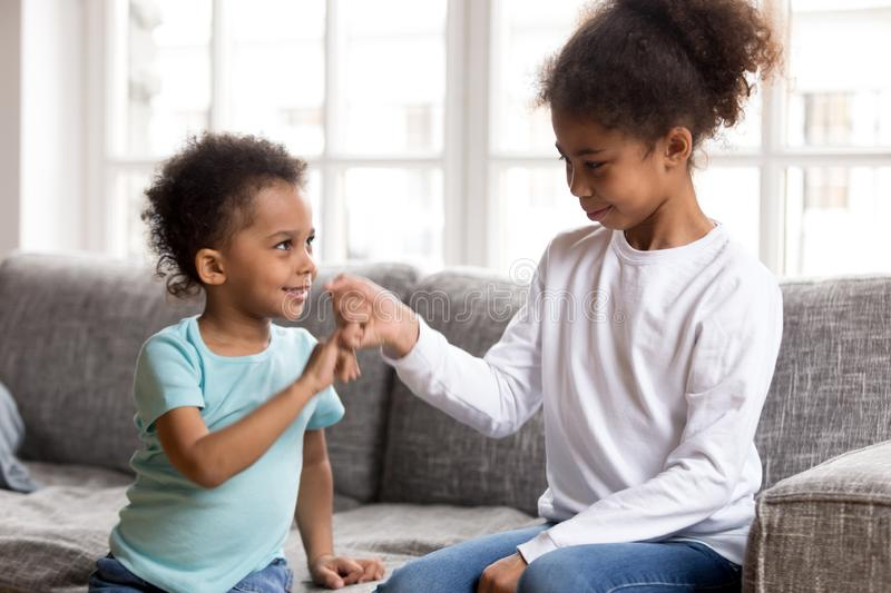 Brother and sister reconcile after fight joining pinkies. Black African little brother and sister sitting on couch at home. Small american children reconcile royalty free stock photo