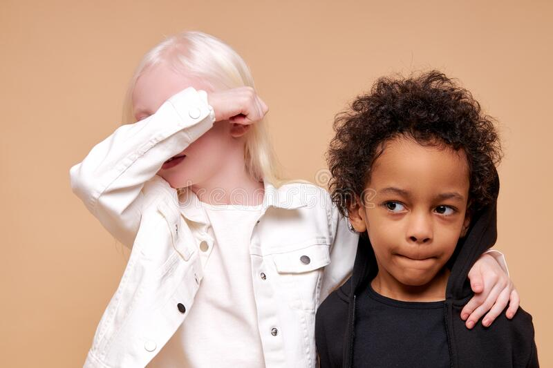 Black afro and albino kids at a loss. Portrait of black afro and albino kids at a loss, girl with unusual appearance closed her eyes with hands and multiracial royalty free stock photos
