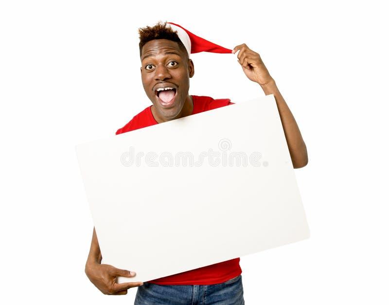 Black afro american man in Christmas Santa hat smiling happy showing blank billboard copy space stock image