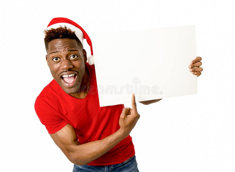Black afro american man in Christmas Santa hat smiling happy showing blank billboard copy space stock image