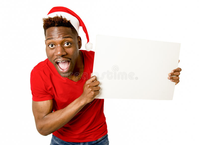 Black afro american man in Christmas Santa hat smiling happy showing blank billboard copy space stock images