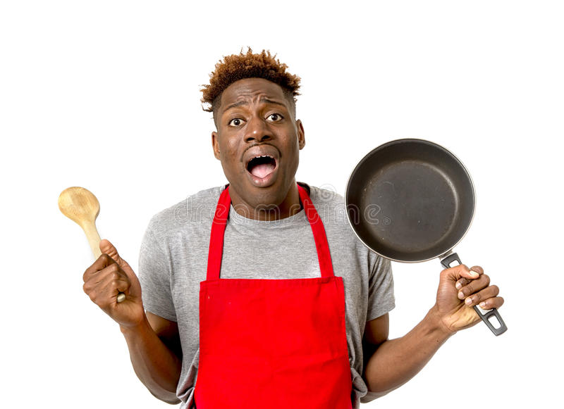 Black afro american man home cook in chef apron cooking pan and spoon lost and overworked royalty free stock image
