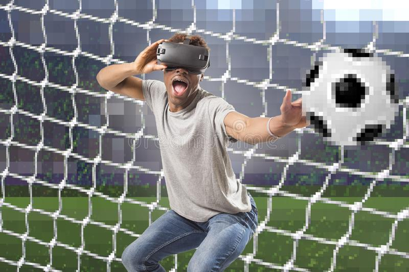 Black afro American man using vr virtual reality 3D goggles playing soccer football video game with pixelated computer goal and st stock image