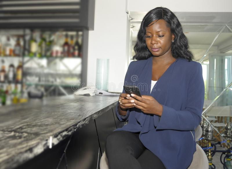 Black Afro American woman on her 30s wearing formal business clothes sitting at resort restaurant bar working with mobile phone royalty free stock photo
