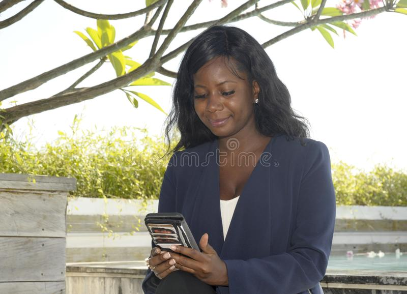 Black Afro American woman on her 30s wearing formal business clothes sitting at resort restaurant working with mobile phone royalty free stock photography
