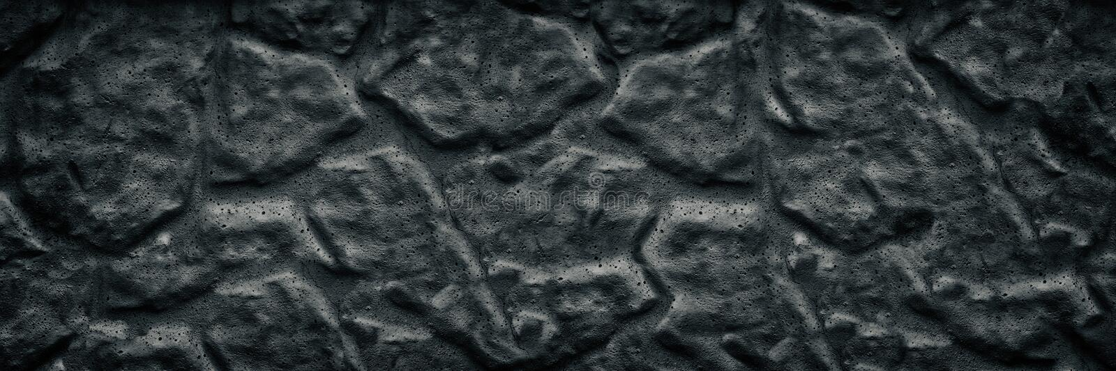 Black aged stone wall wide texture. Dark rough surface long background stock image