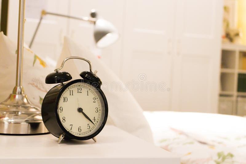 Black alarm clock on the bedside table. With background the white bed in the room royalty free stock photo