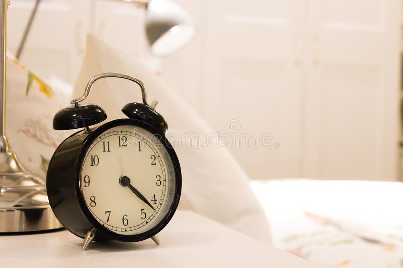 Black alarm clock on the bedside table. With background the white bed in the room stock photos