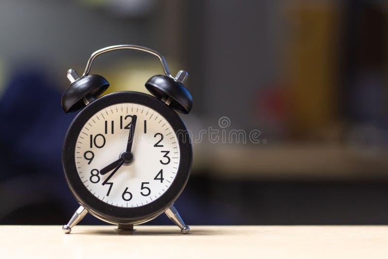 Black Alarm Clock on desk table stock photo