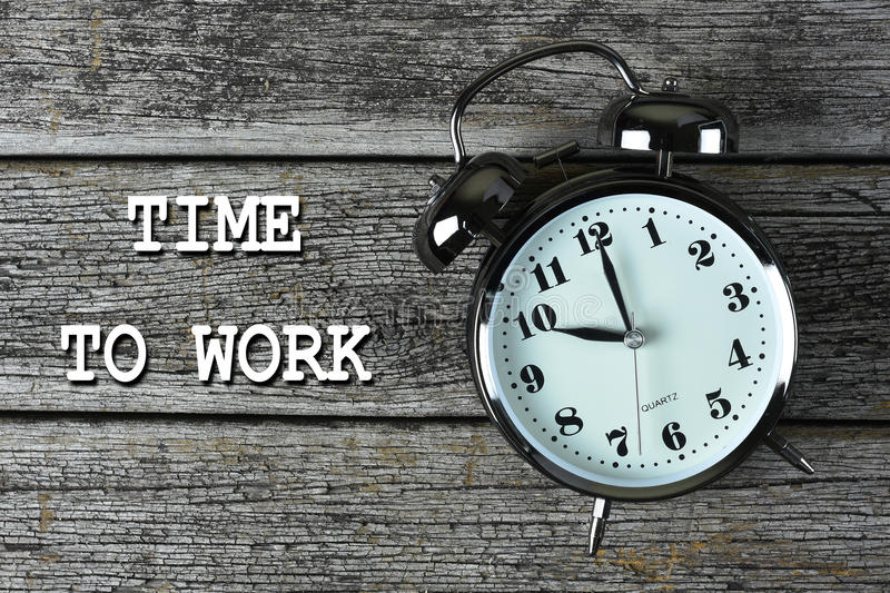 Black alarm clock on the rusty wooden table with word TIME to WORK.  stock photos