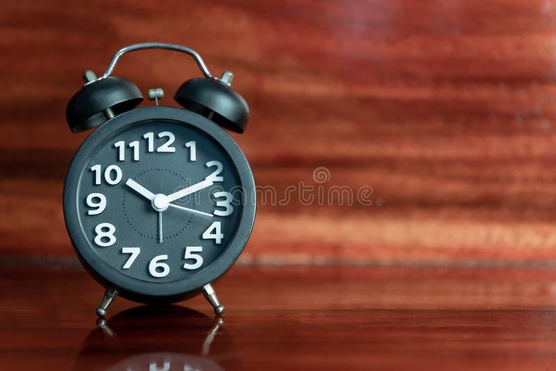Black Alarm clock on wooden floor royalty free stock photos