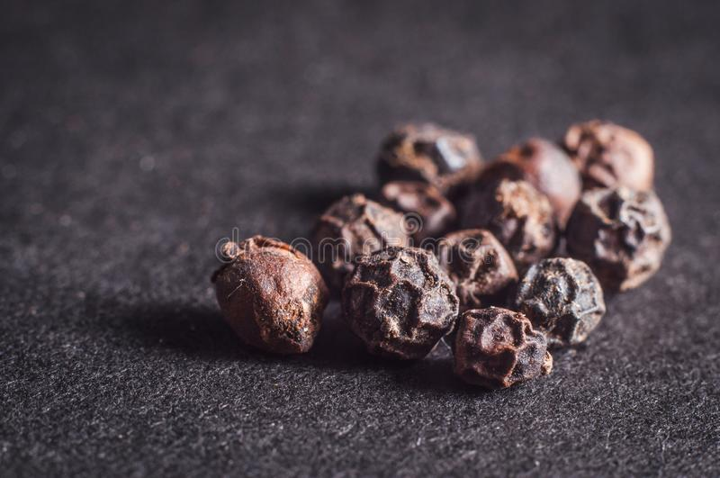 Black allspice in a pile on a dark background.  stock photography