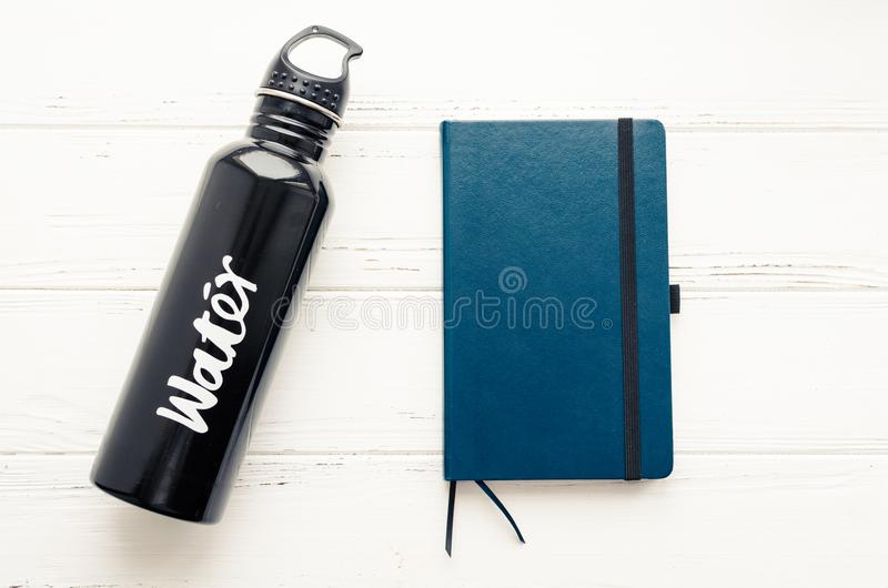 Black aluminum reusable water bottle and notebook royalty free stock photos