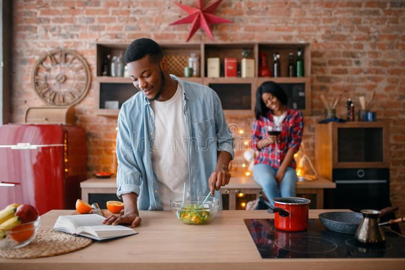 Black american love couple cooking on the kitchen. Black american love couple cooking together on the kitchen. African family preparing vegetable salad at home royalty free stock images