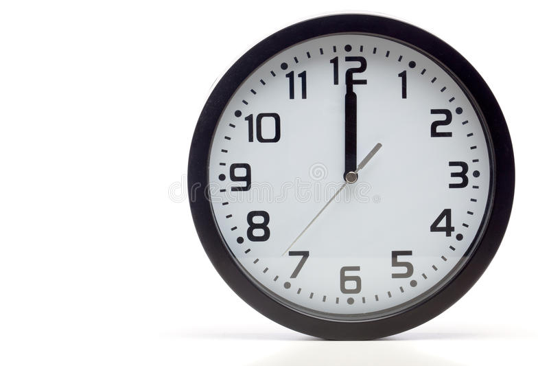 Black analog clock. Analog clock with black frame, showing time of 12 o'clock sharp, noon or midnight. Cutout, studio shot, isolated on white background stock photography