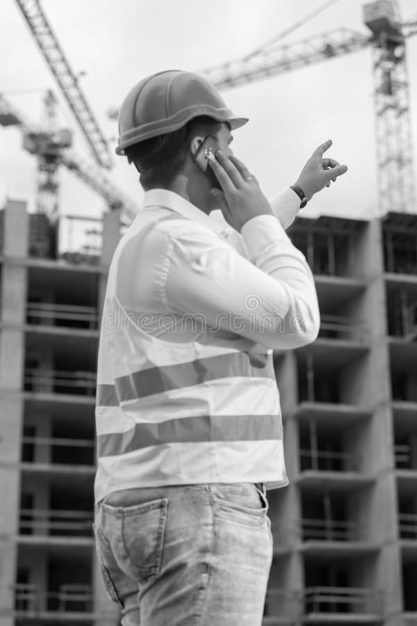 Black anf white rear view portrait of construction engineer talk stock photography