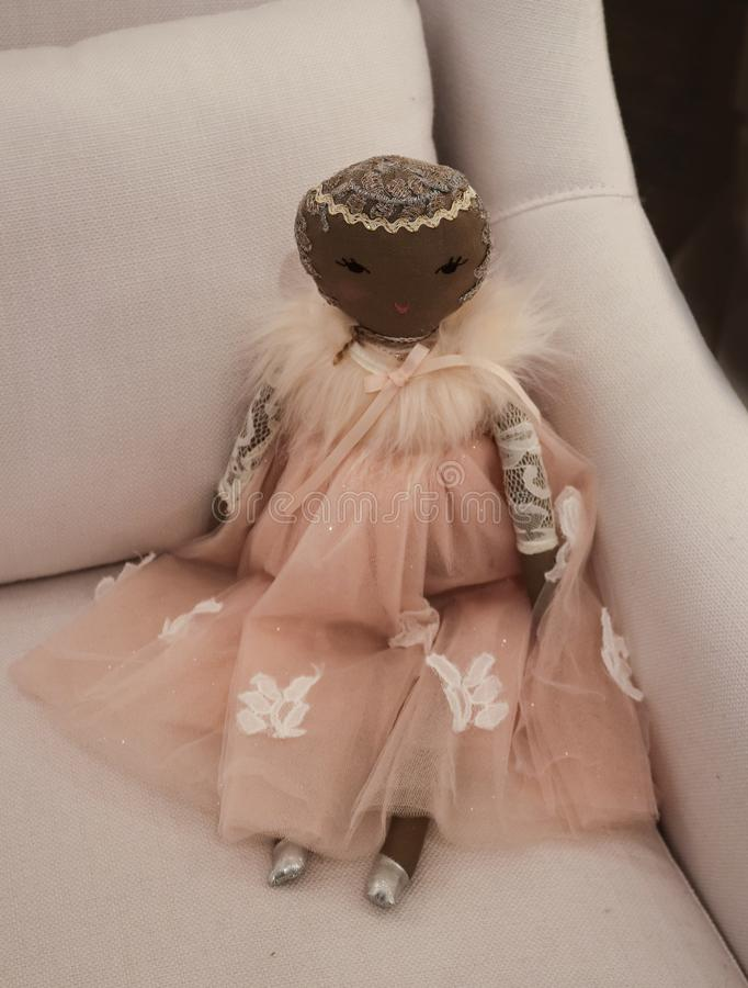 Black angel doll dressed in pink with silver sparkles in a white linen chair. Black angel doll dressed in pink with silver sparkles sitting in a white linen royalty free stock photography