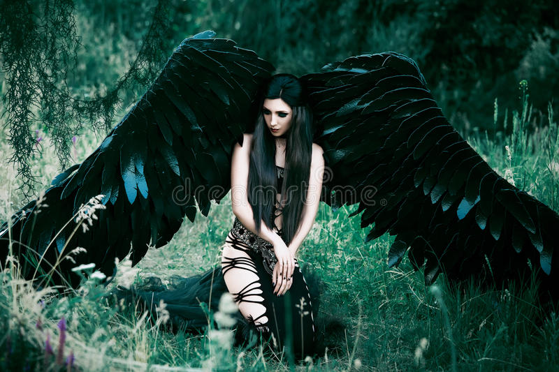Black Angel. Pretty girl-demon. With black wings. An image for Halloween. Image of an old book of fairy tales. Fashionable toning with noise royalty free stock images
