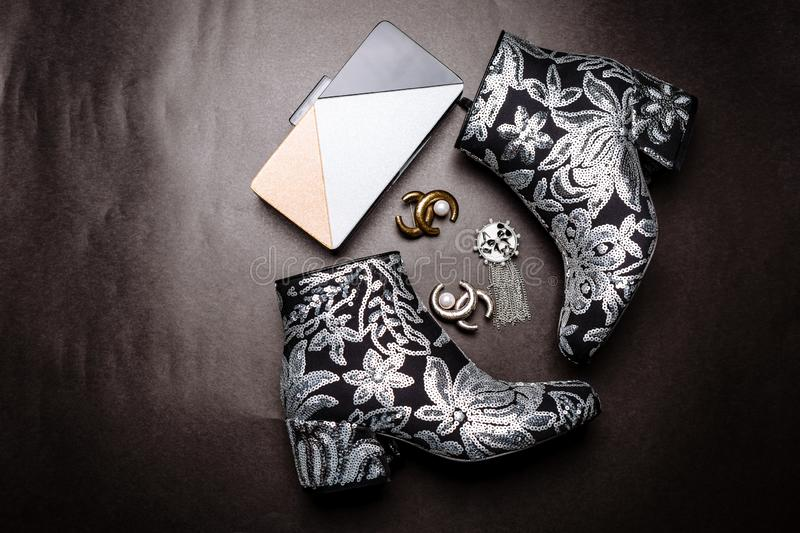 Black ankle boots with thick heels decorated with flowers embroidered with silver sequins and a metal clutch and brooches on a stock photos