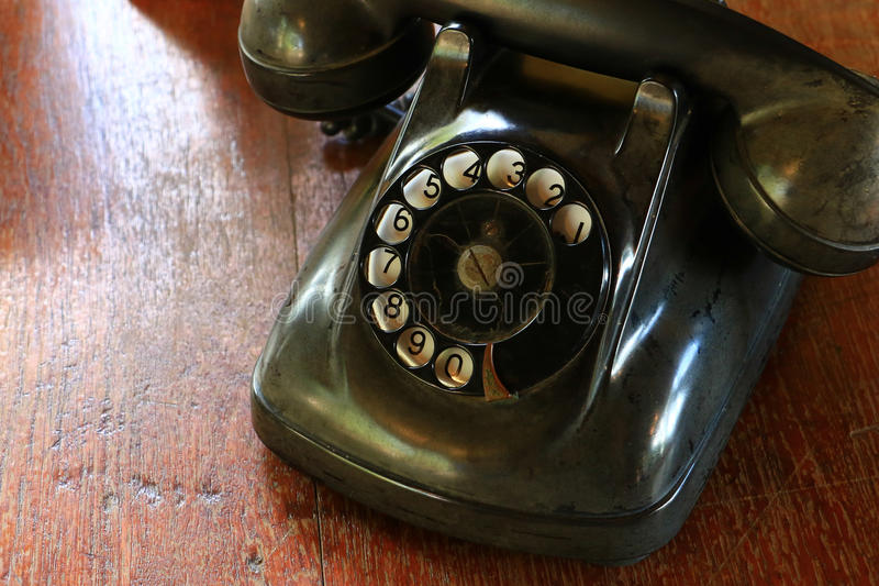 Black antique vintage analog telephone dialing or scrolling phone on wooden table. Contact us concept royalty free stock photos