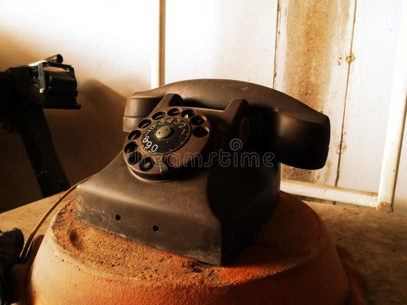 Black antique vintage analog telephone. Dialing or scrolling phone on wooden table,Contact us concept stock image