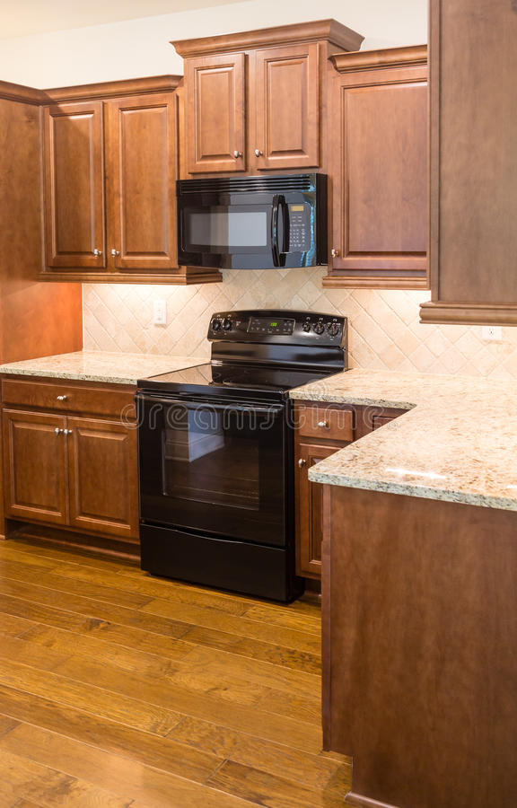 Black Appliances in New Kitchen. New kitchen with modern appliances and hardwood floors royalty free stock photo