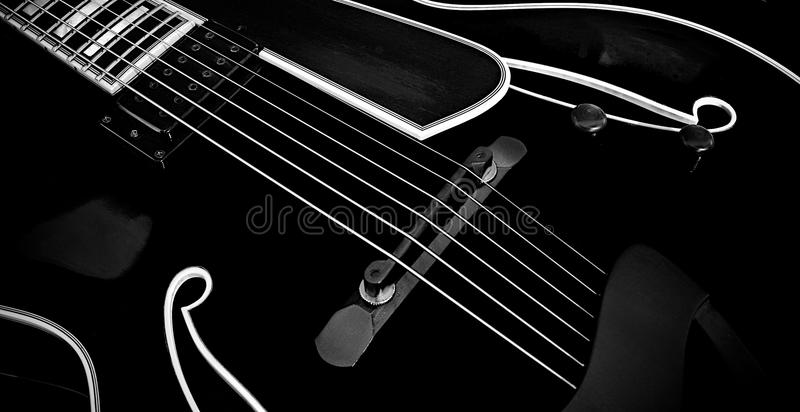 Black Archtop Guitar - 02. Cropped view of a black jazz/archtop guitar royalty free stock photography