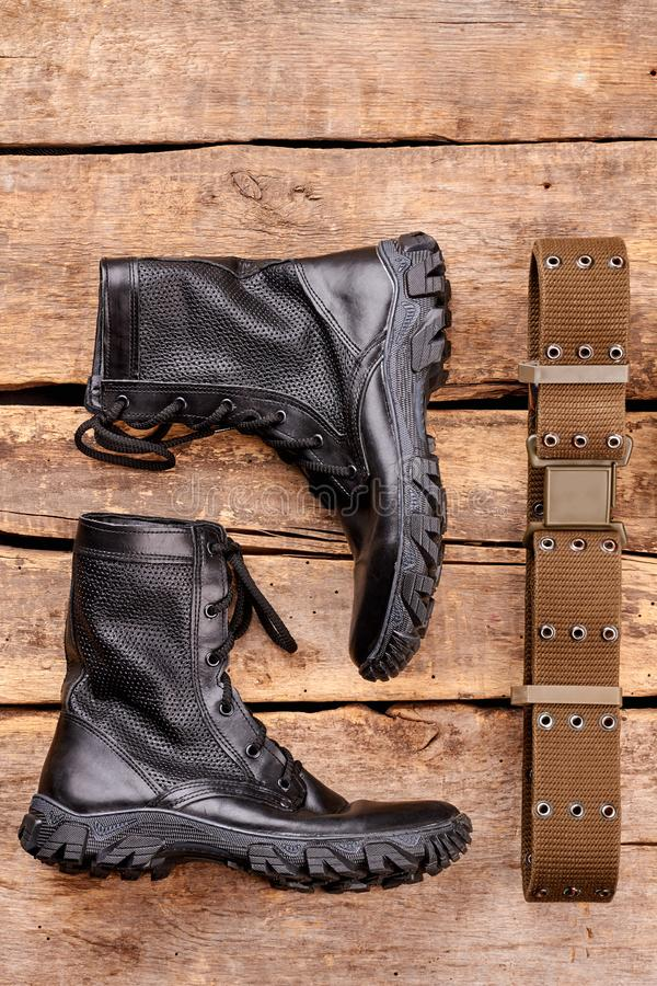 Black army boots and strap on wood. royalty free stock photography