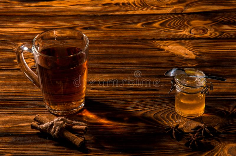 Black aromatic tea in a glass transparent cup. Glass jar with gold honey on a rustic brown wooden table. Copy space royalty free stock photo