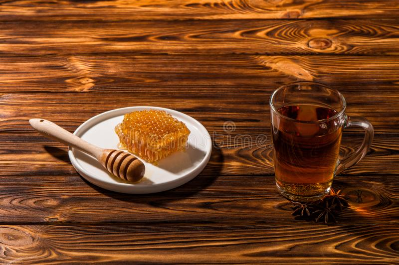 Black aromatic tea in a glass transparent cup. White plate with gold honey on a wooden background. Copy space royalty free stock photo