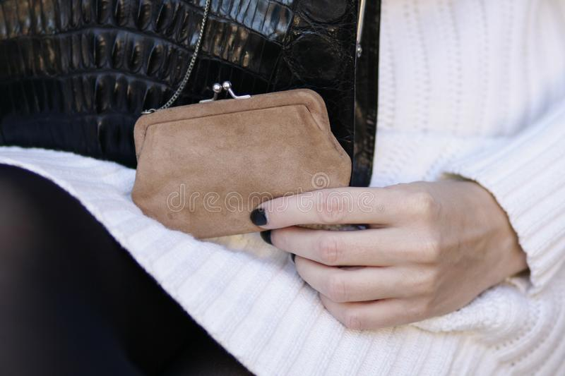 Black art deco crocodile purse and white sweater fashion detail stock images