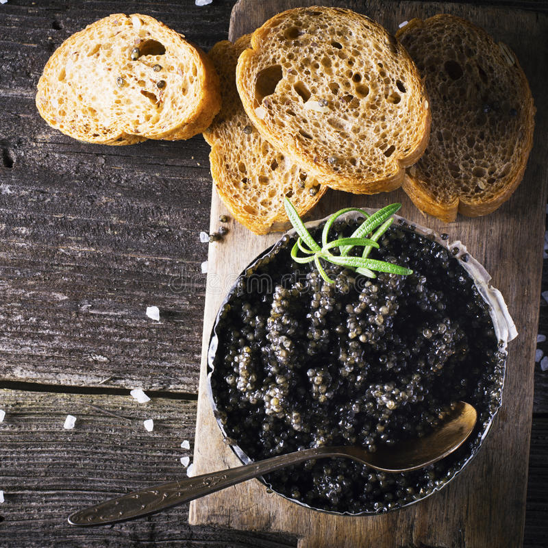 Black Astrakhan Russian salted sturgeon caviar in a can on dark background with wooden spoon and slices of bread. Snacks. Black Astrakhan Russian salted sturgeon royalty free stock photos
