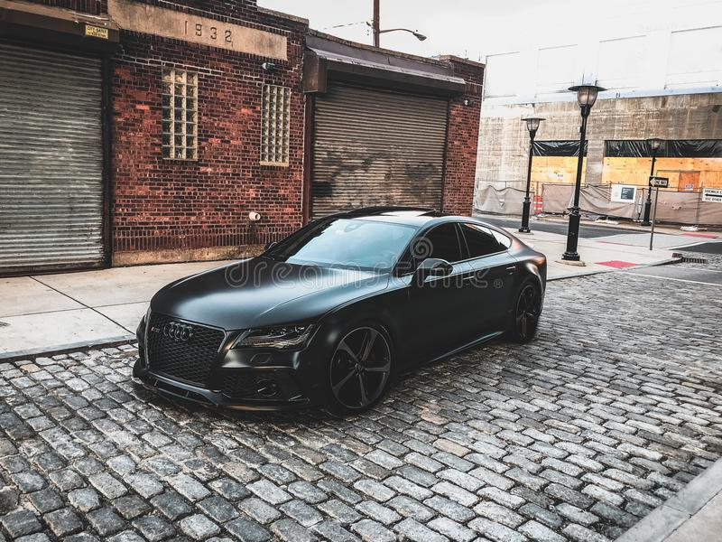 Black Audi A-series Parked Near Brown Brick House royalty free stock photography