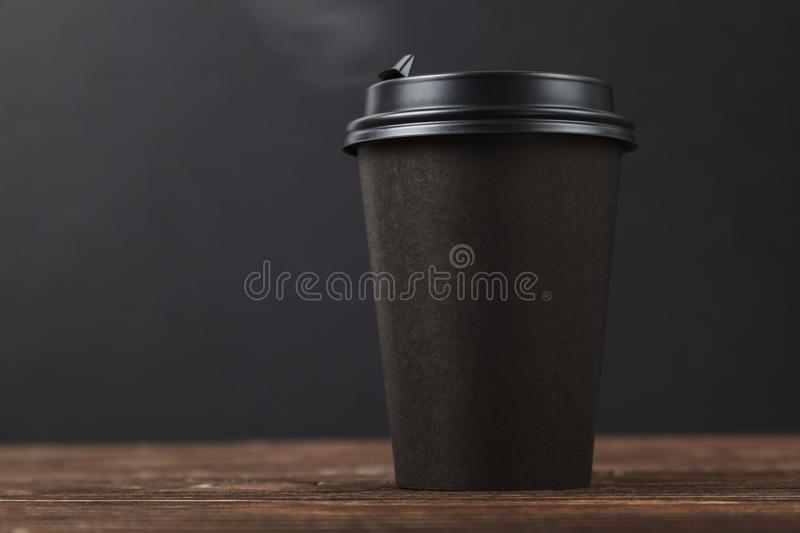 Black background, hot take-away coffee on a wooden table. Cafe menu design concept stock photography