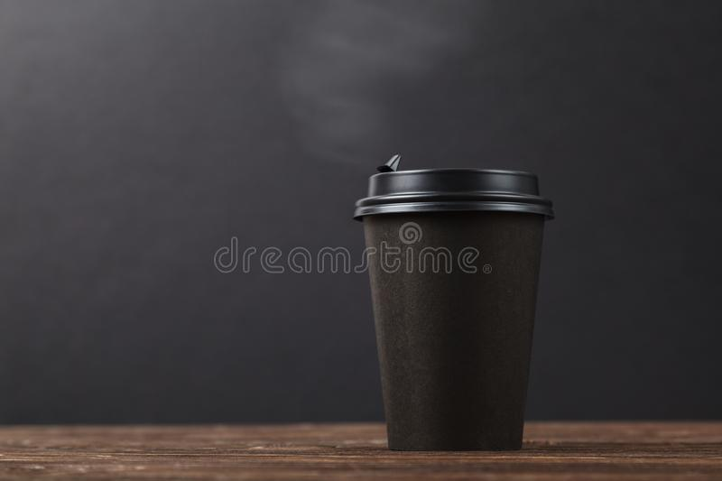 Black background, hot take-away coffee on a wooden table. Cafe menu design concept royalty free stock photo