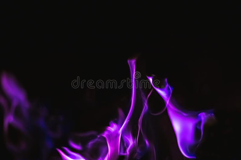 Black background image of purple fire forms stock images
