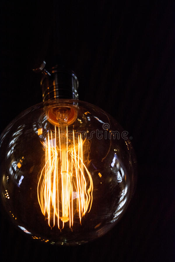 On a black background light bulb Tesla. Place for the text. These Edison style bulbs are beautiful but are high consume electrici. Ty also stock images