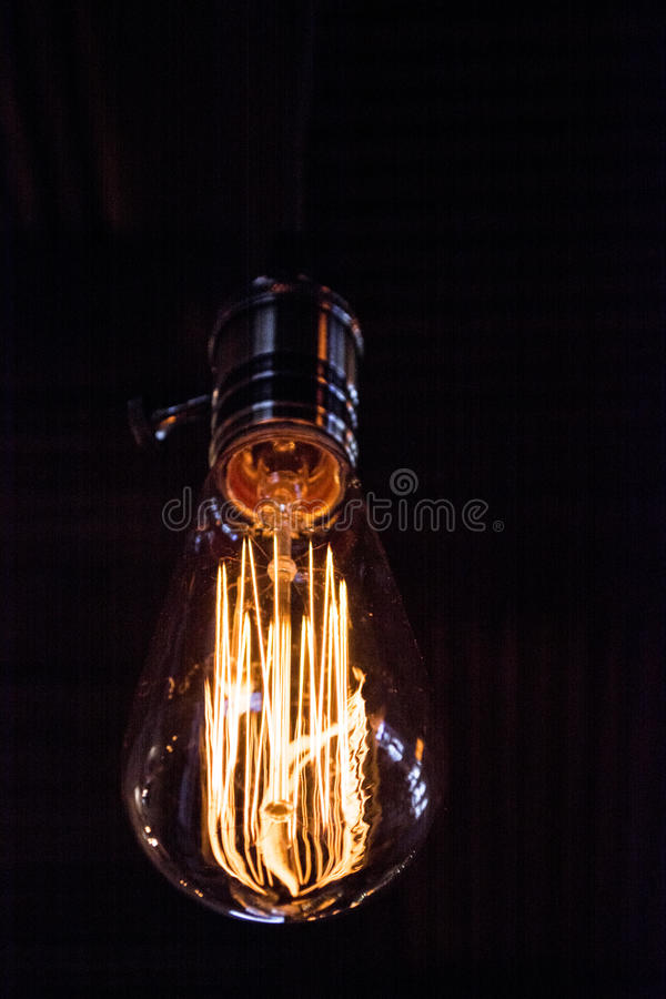 On a black background light bulb Tesla. Place for the text. These Edison style bulbs are beautiful but are high consume electrici. Ty also royalty free stock photo
