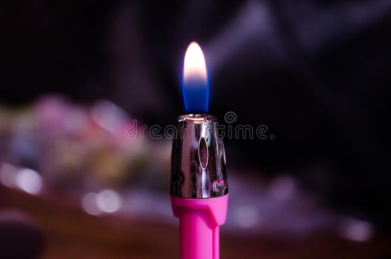 Black background and lighter. Flame. Lighter. Tongue of flame Fire burns. Burning lighter. stock photography