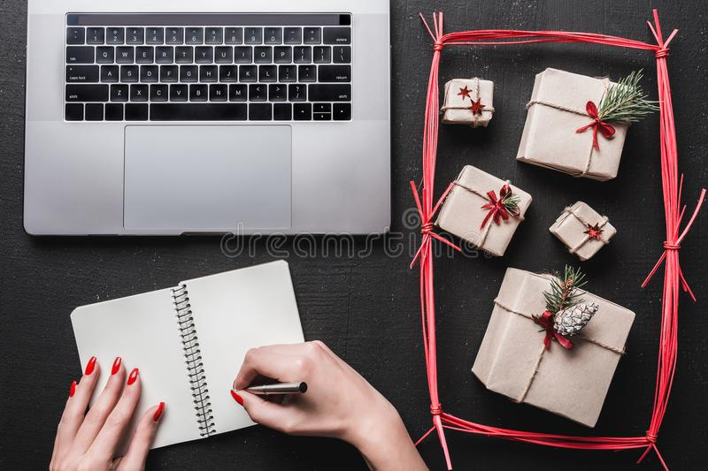 On black background, many gifts and computer. On a book, a lady`s hands want to write. On black background, many gifts and computer. On a book, a lady`s hands stock photo