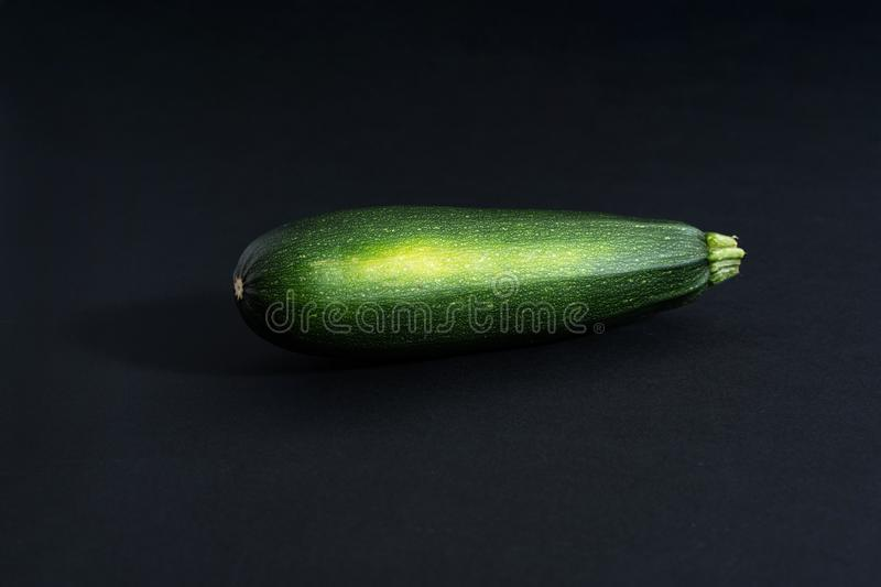 On a black background one raw green whole zucchini,. Close-up top view, copy space, horizontal frame stock image