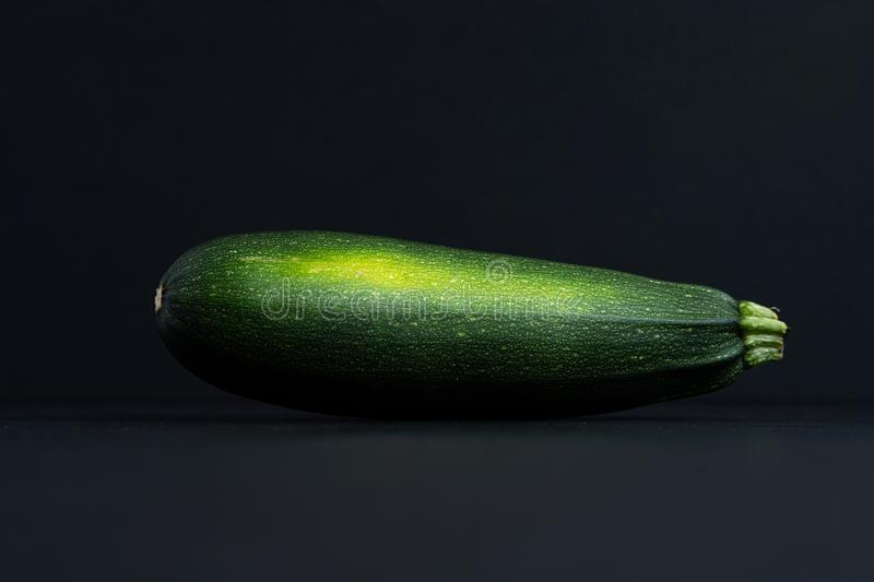 On a black background one raw green whole zucchini,. Close-up top view, copy space, horizontal frame royalty free stock photography