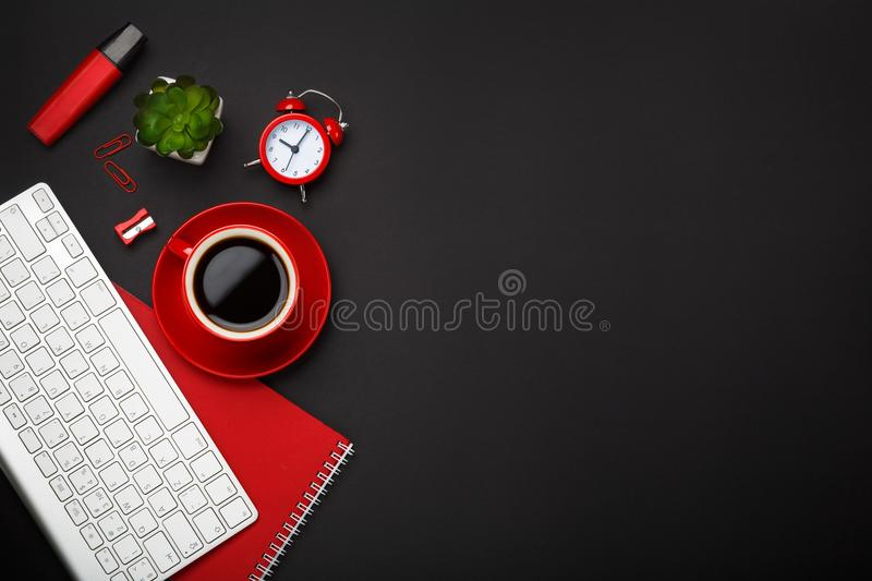 Black background red coffee cup note pad alarm clock flower keyboard blank space desktop stock photography