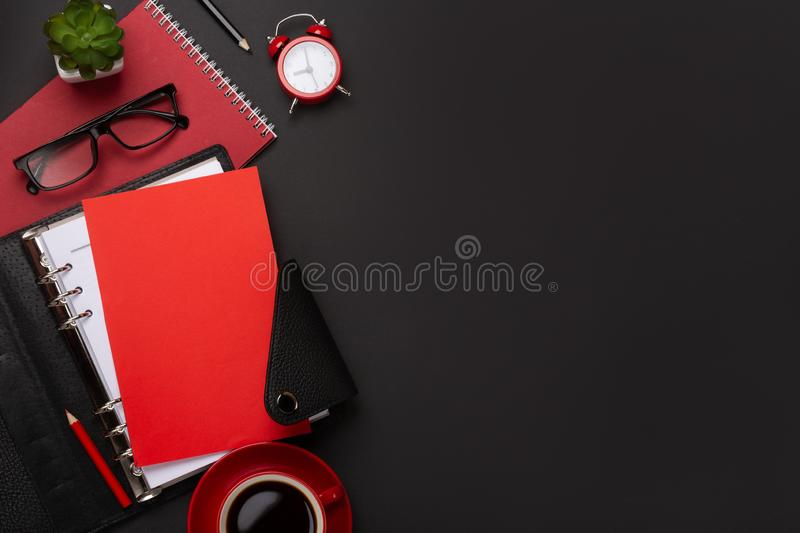 Black background red coffee cup notepad alarm clock flower diary scores keyboard on the table. Top view with copy space.  stock images