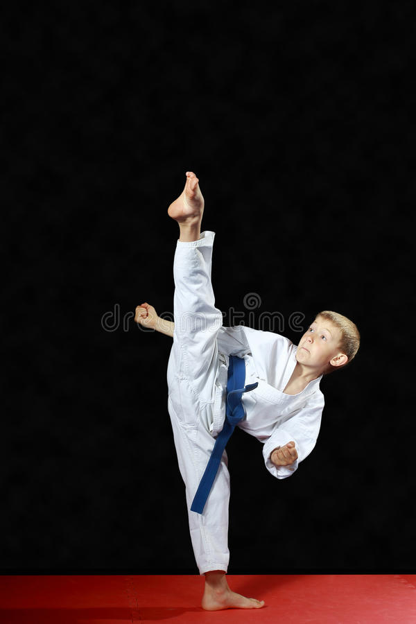 On a black background and red mat the boy beat blow leg mawashi geri. On red and mat a black background the boy beat blow leg mawashi geri royalty free stock photography