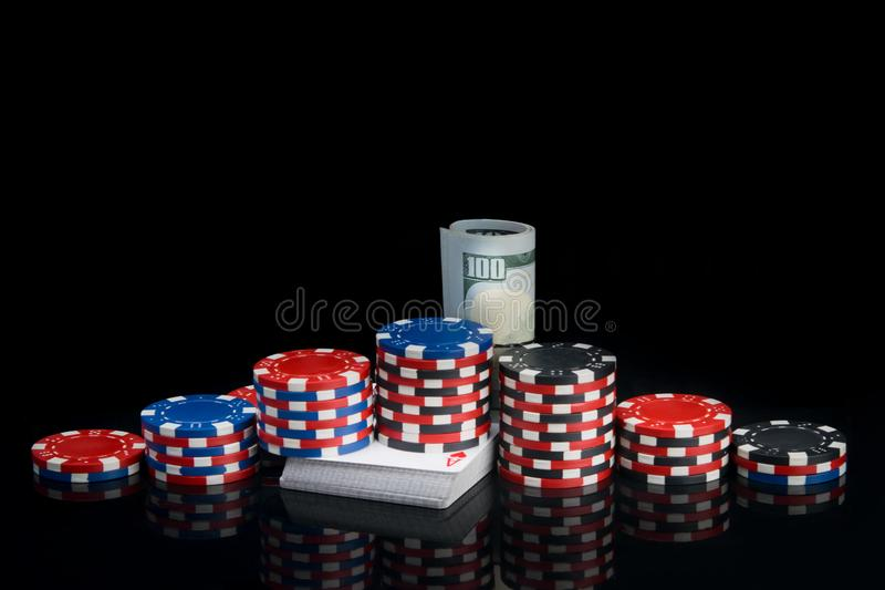 On a black background with a reflection, on a deck of cards, there are pyramids of colored chips and dollar bills wrapped in a. Roll for playing poker stock images