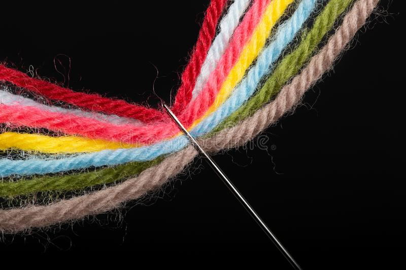 On a black background, several bright multicolored woolen threads are pass through the eye of the needle. Close-up stock images