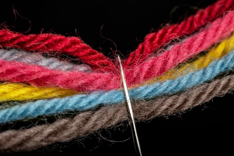 On a black background, several bright multicolored woolen threads are pass through the eye of the needle. Close-up royalty free stock image